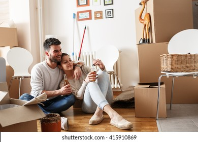 Young couple Moving in new home.Sitting on floor and relaxing after cleaning and unpacking.