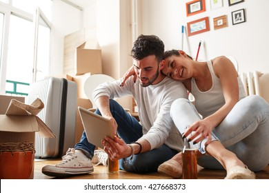 Young couple moving in new home.Sitting on floor and relaxing after cleaning and unpacking.Using tablet.