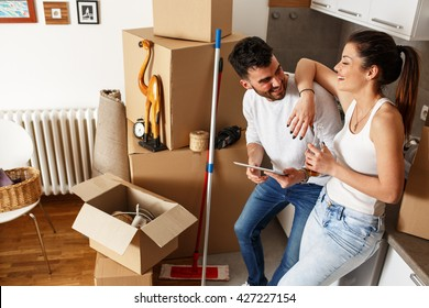 Young couple Moving in new home.Standing by the kitchen and relaxing after cleaning and unpacking.Looking something on tablet.