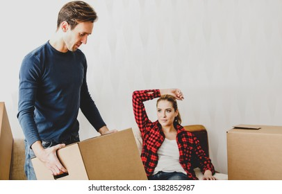 Young couple moving on. Man carrying box while woman resting.