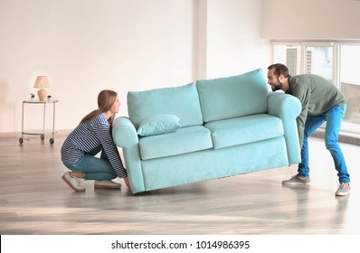 Young couple moving sofa in room at new home