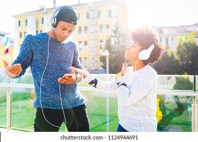 young couple multiracial listening music dancing outdoor back light using headphones and smart phone - happiness, technology, interaction concept