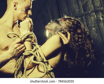Young couple of muscular handsome man and sexy woman with paited face and bare body with rope on hands