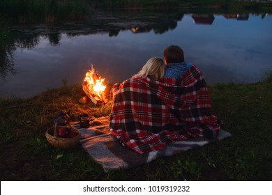Young couple near bonfire camp romantic evening together twilight bright fire in nature bokeh from the fire . blurred backgrounds . Space views. Scouts