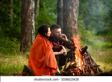 Young couple near bonfire camp romantic evening together bright fire in nature, blurred background. Couple in love covered with plaid sit near bonfire. Man with beard smoking cigarette. Picnic concept