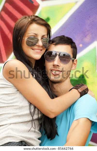 Young couple near graffiti background.