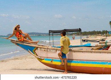 Young couple near the old boat on the shore of the ocean