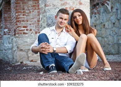 Young couple near ruined brick wall
