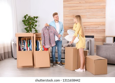 Young couple near wardrobe boxes at home