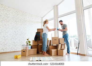 Young couple in new apartment unpacking cardboard boxes