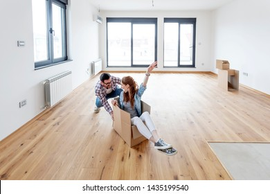 Young couple in new empty room. She is sitting on card box while he pushing her from behind