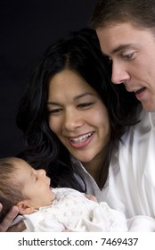 A young couple with a newborn girl. Family, love, caring.