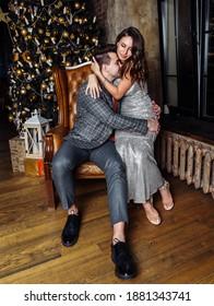 young couple newlyweds laugh rejoice having fun Christmas mood hug tenderness love kiss Christmas tree
