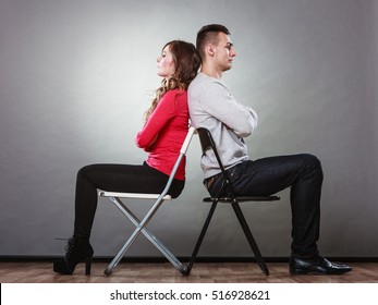 Young couple not talking to each other and sitting back to back after arguement. Disagreement in relationship. Man and woman get mad.