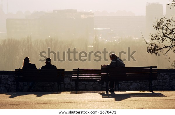 Young couple and older man sittin on bench in park