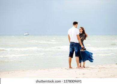 Young couple on the beach talking to each other.