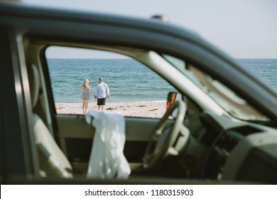 Young couple on the beach. View from the car
