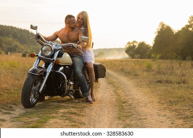 Young couple on a beautiful motorcycle in the field. Love and sincere feelings. Photo for motorcycle and social magazines and websites.