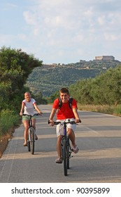 Young couple on bicycle ride through countryside in Mediterranean Europe
