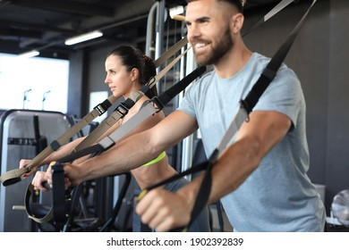 Young couple on body training with trx in gym