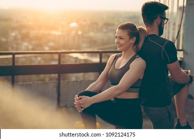 Young couple on a building rooftop terrace stretching before workout; urban skyline in the background.
