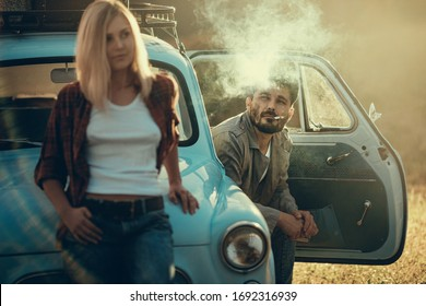 Young couple on a car trip. She leaned against the car's hood, he sits on driver's seat and smokes, selective focus on a man