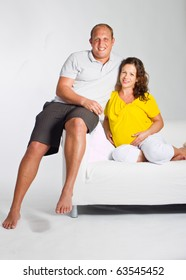 Young couple on a couch. The woman is pregnant and they seem to be in love.