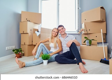 Young couple on the floor in a new house. Housewarming.