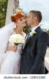 Young couple on a formal wedding photo  The groom kisses his bride while her eyes are closed