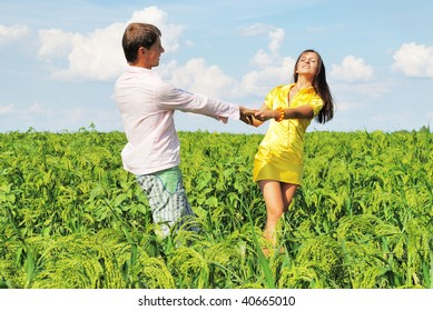 Young couple on green field in sunny day