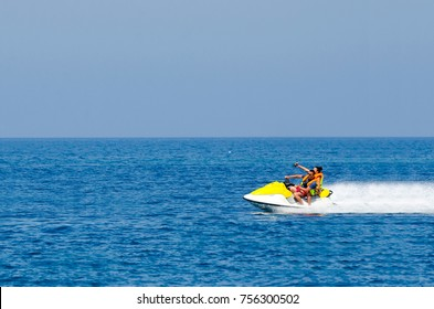 Young Couple on Jet Ski fast ride, Tropical Ocean, Vacation Concept