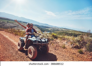 Young couple on an off road adventure. Man driving quad bike with girlfriend sitting behind and enjoying the ride in nature.