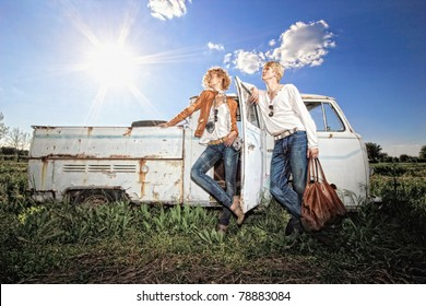 A young couple on a old broken car in a field man is holding a leather bag