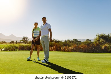 Young couple on putting green at golf course. Male and female golfers at field on sunny day.