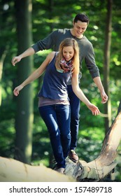 young couple on a romantic date in the forest balancing over a tree trunk