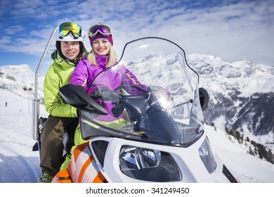 Young couple on a snowmobile ski resort
