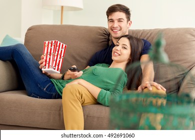 Young couple on the sofa and eating popcorns