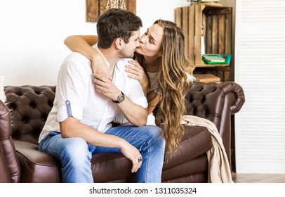 Young couple on the sofa in love. Couple in love sitting on the couch and hugging