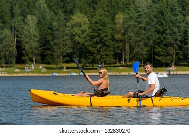 Young couple on summer weekend kayaking on pond