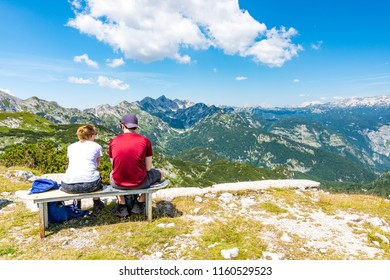 Young couple on top of mountain is looking to far hill. Slovenia mountain Vogel, Triglav and near Bohinj lake.