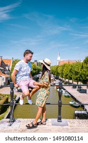 young couple on vacation Friesland Netherlands Sloten, old town of Sloten Netherlands with canals and windmill