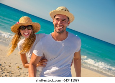 Young couple on vacation laughing and having fun on the beach one summer day.