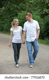 Young couple on a walk - both run hand in hand and smiling and there.