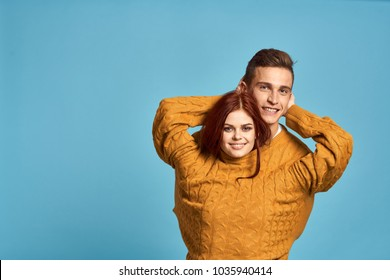 young couple in one sweater on a blue background
