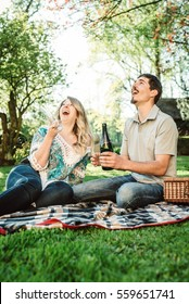 Young couple open champagne bottle during a picnic in park