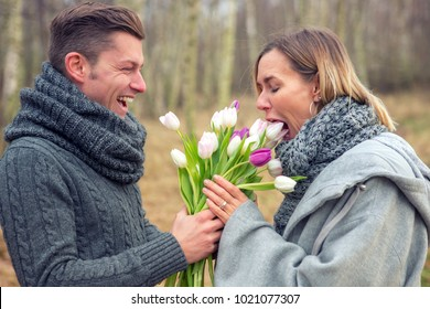 young couple outdoors with flowers being silly and happy