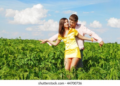 Young couple outdoors playing on a spring meadow