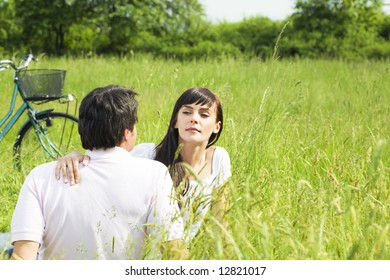 Young couple outdoors sitting in meadow, woman looking around. Copy space