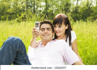Young couple outdoors, woman taking photo with mobile phone
