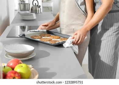 Young couple with oven sheet of homemade cookies in kitchen, closeup